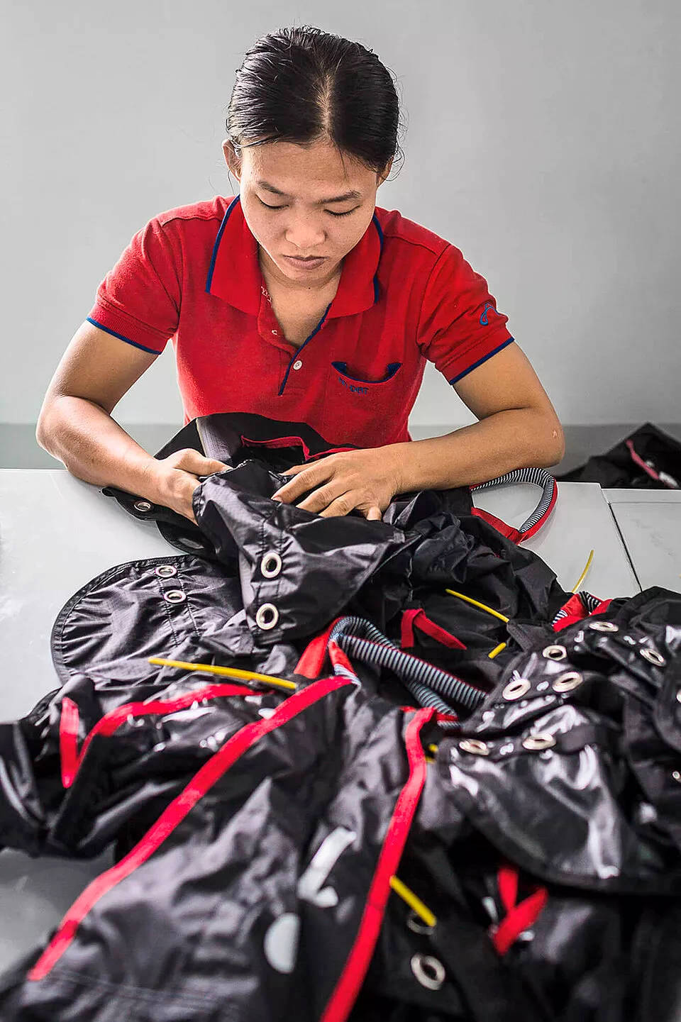 Skilled Advance factory worker assembling reserve container for harnesses